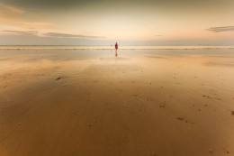 Lonley woman walking on the beach over sunset